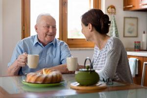 Female caregiver helping senior man, kitchen