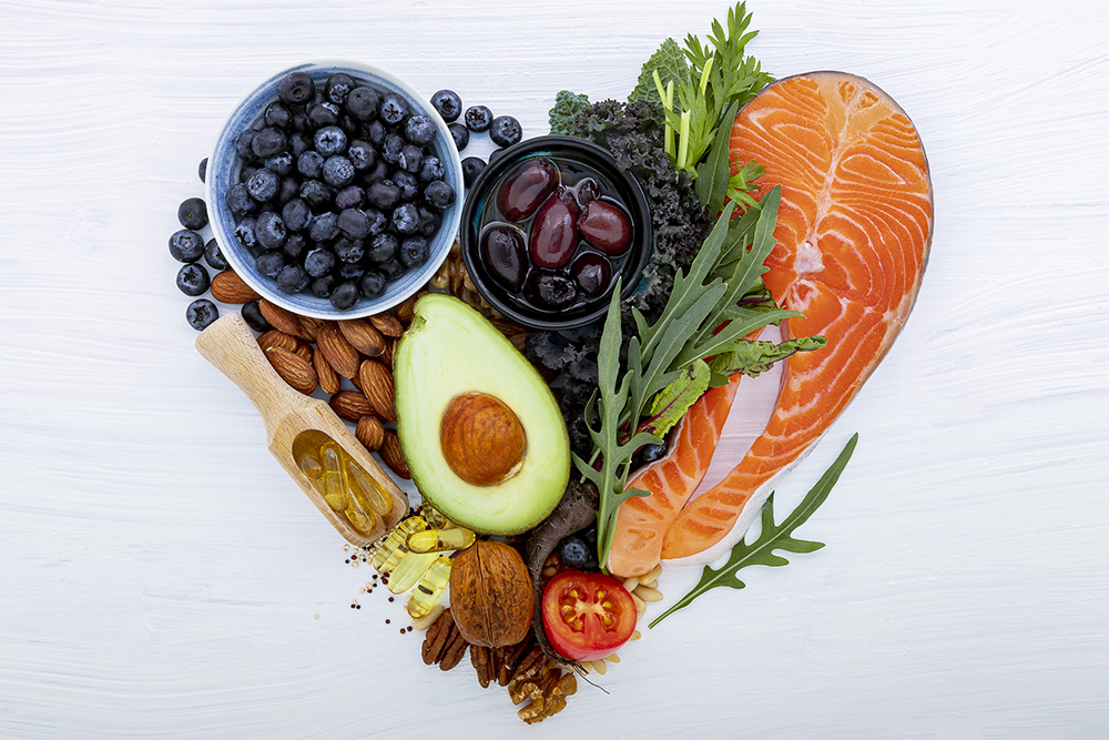 Heart shape of ketogenic low carbs diet concept. Ingredients for healthy foods selection on white wooden background. Balanced healthy ingredients of unsaturated fats for the heart and blood vessels.