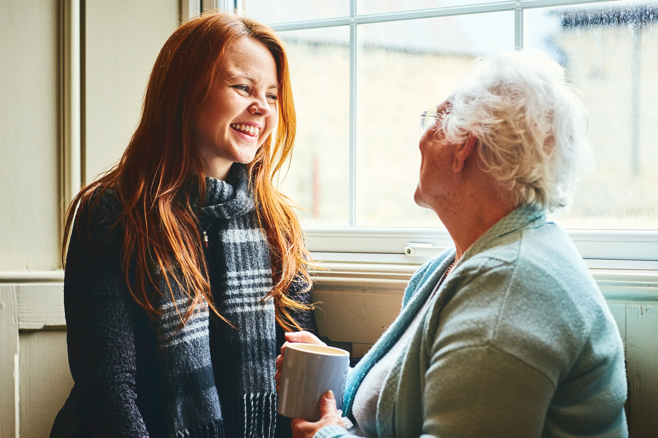 Young caregiver talks to senior woman about at-home care solutions.